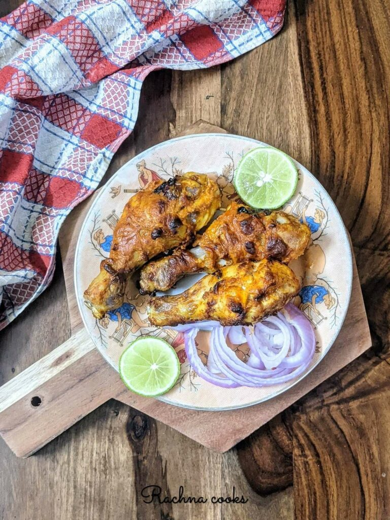 tandoori chicken drumsticks nice and brown on a plate with garnish of onion rings and lemon wedges.