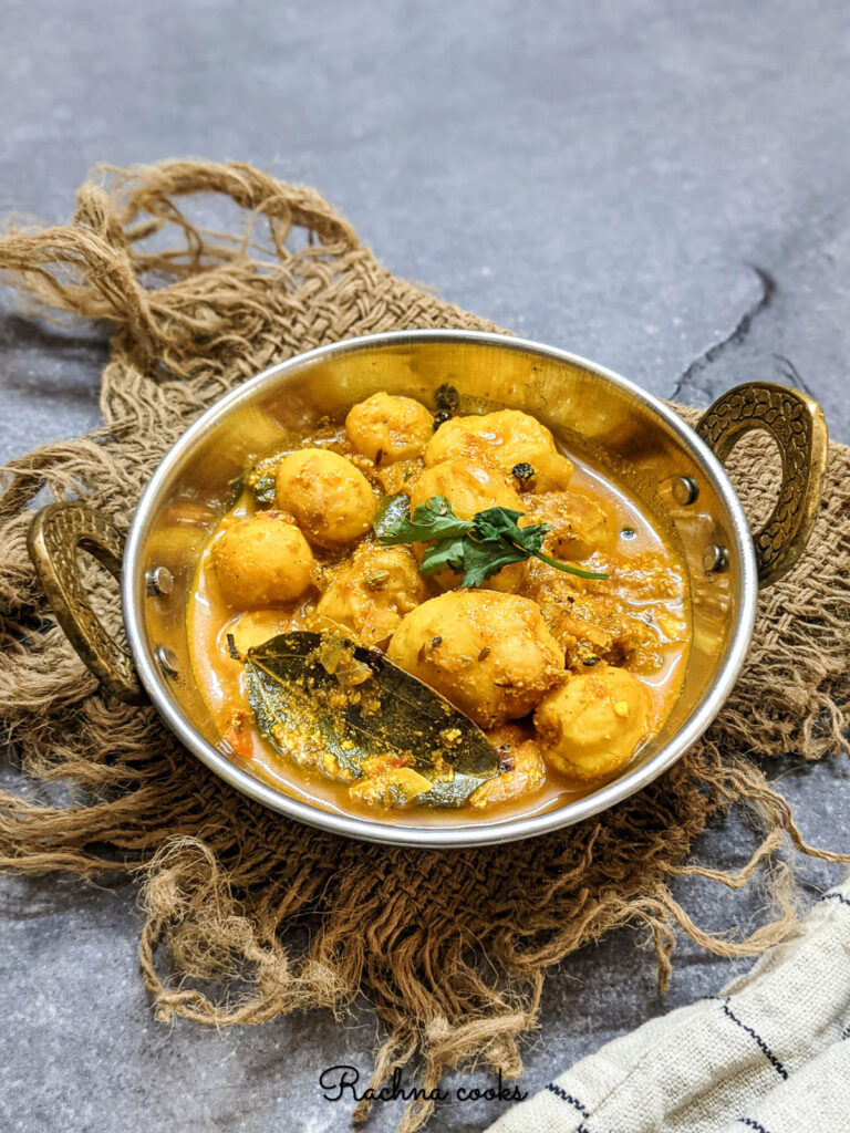 Tasty dum aloo curry in a kadhai against a grey background.