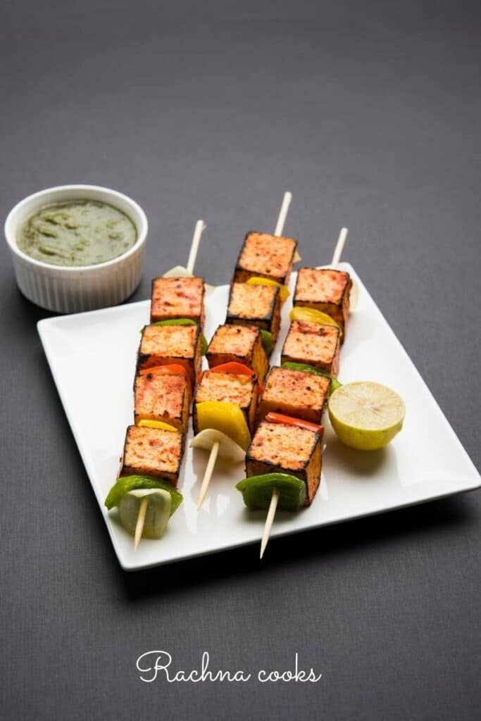 Skewers of paneer tikka with peppers on a white plate served with green chutney and lemon.