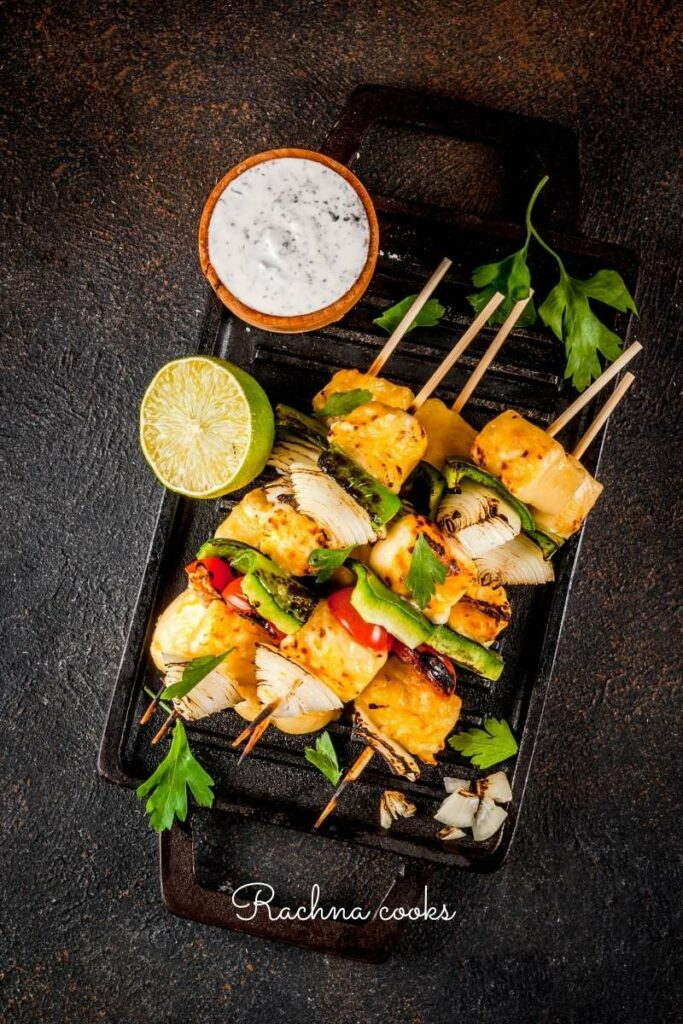 Skewers of paneer tikka with onion and capsicum on a black plate