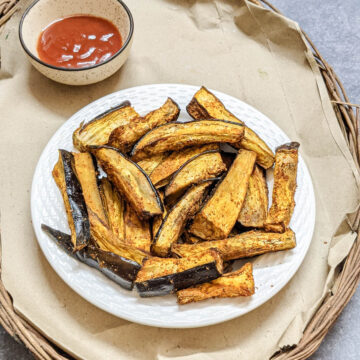 air fried eggplant fries golden on a white plate with ketchup in the background