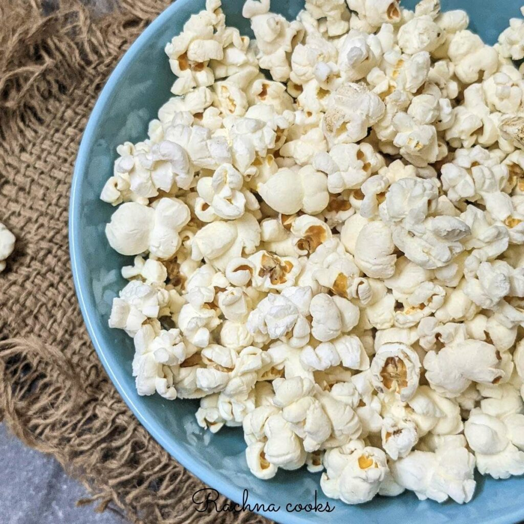 Close up of popcorn in a blue bowl with a brown mat in the background.