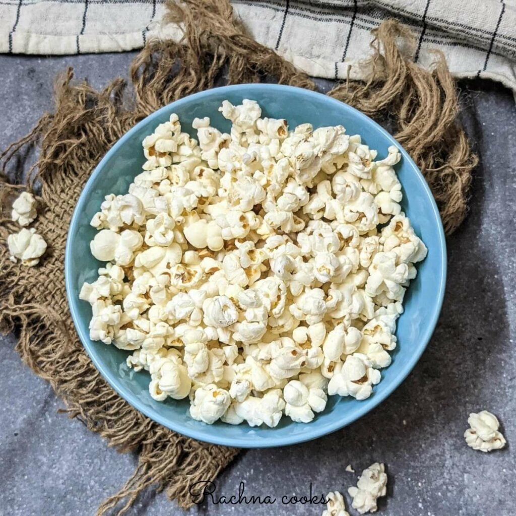 Popcorn in a blue bowl against a brown mat.
