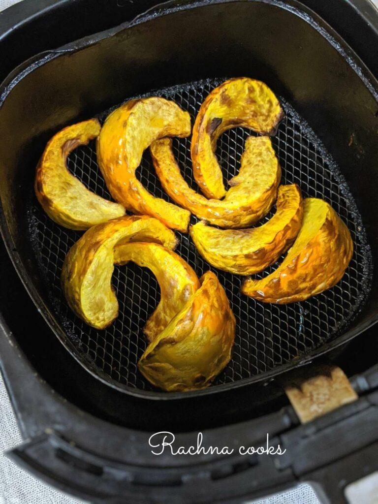Browned and roasted pumpkin wedges in the air fryer basket.