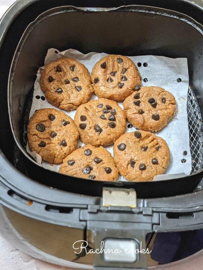 Peanut butter cookies arranged on parchment paper in air fryer basket.