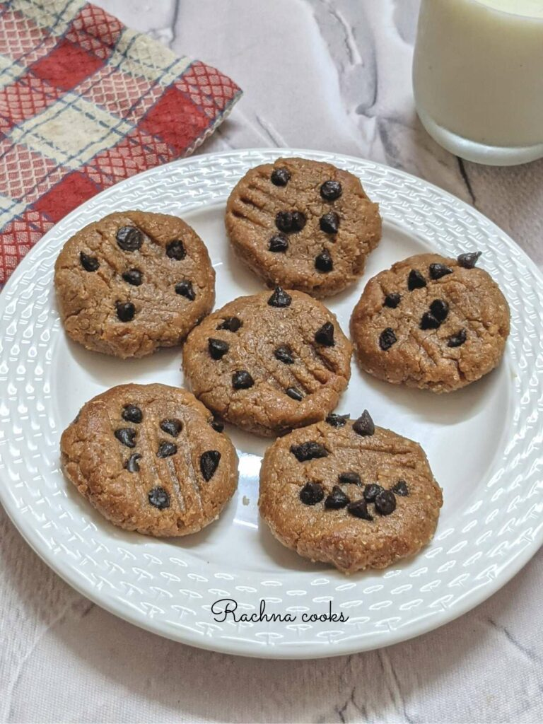 Peanut butter cookies with chocolate chips on a white plate with a glass of milk in the background and a checked red and white napkin.