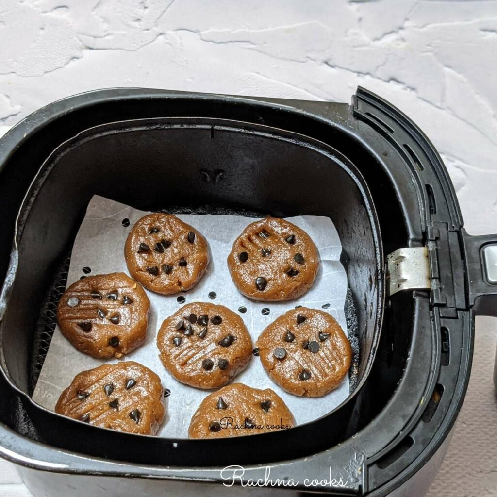 Peanut butter cookies arranged on parchment paper in air fryer basket ready for air frying.