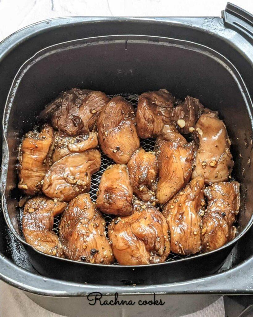 Marinated chicken pieces in air fryer basket