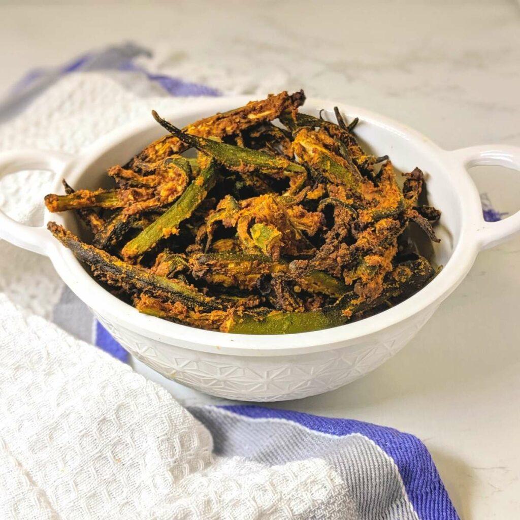 Slivers of crispy air fried okra in a white wok.