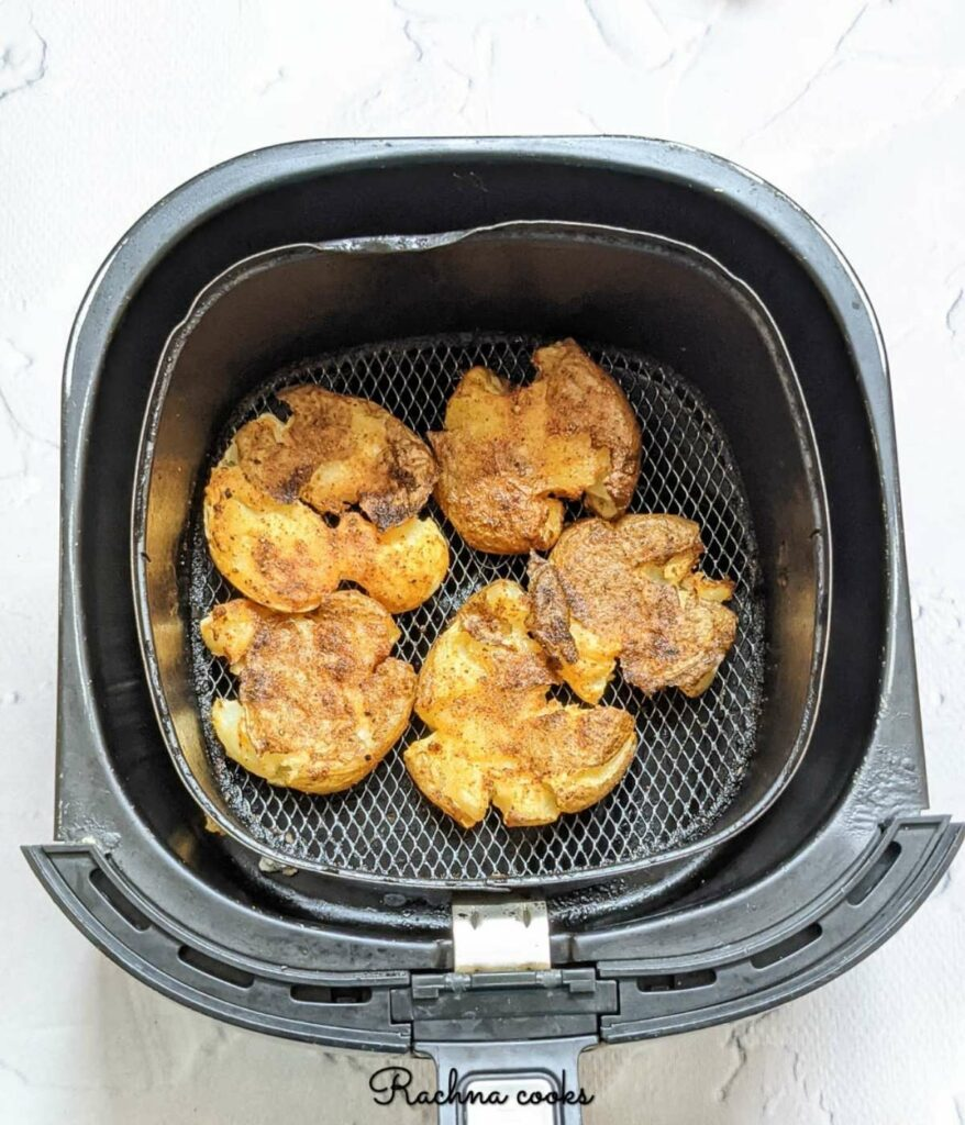 air fried smashed potatoes golden and crispy in air fryer basket.
