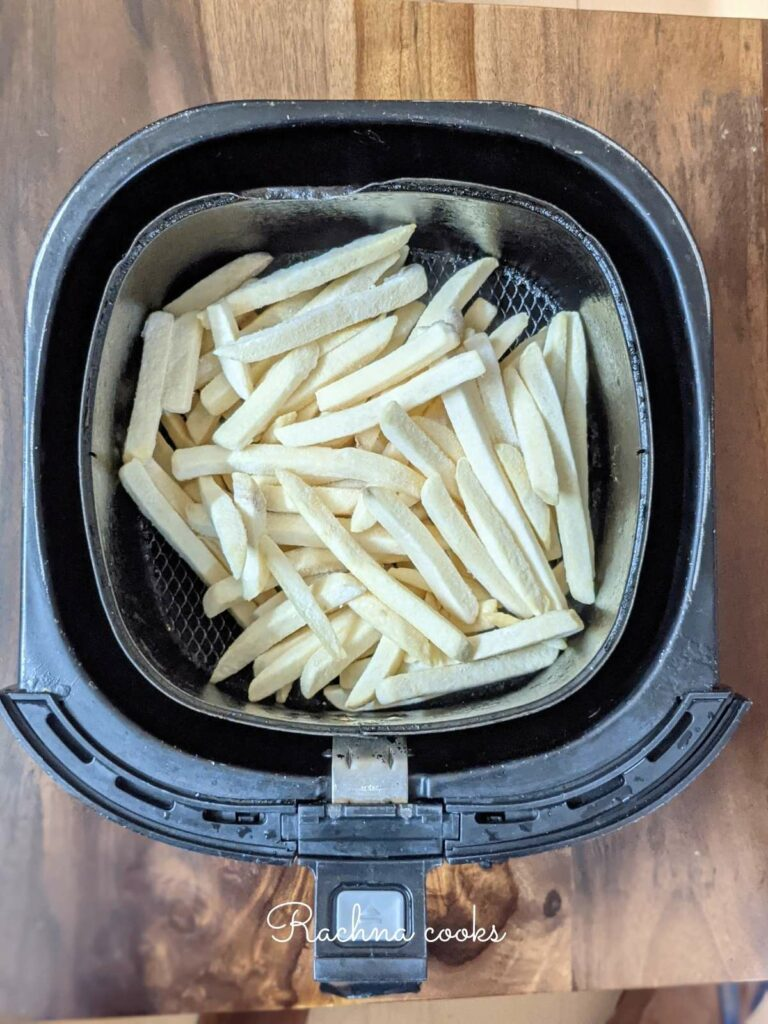 Frozen french fries laid in air fryer basket ready for air frying.