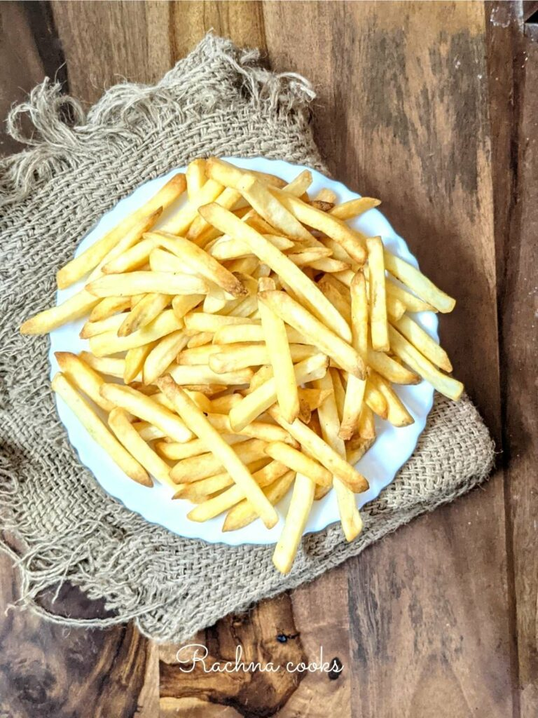 Crispy french fries done in air fryer from frozen in a white plate against a brown background..