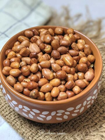 a bowl of roasted peanuts in air fryer with a spicy coating.
