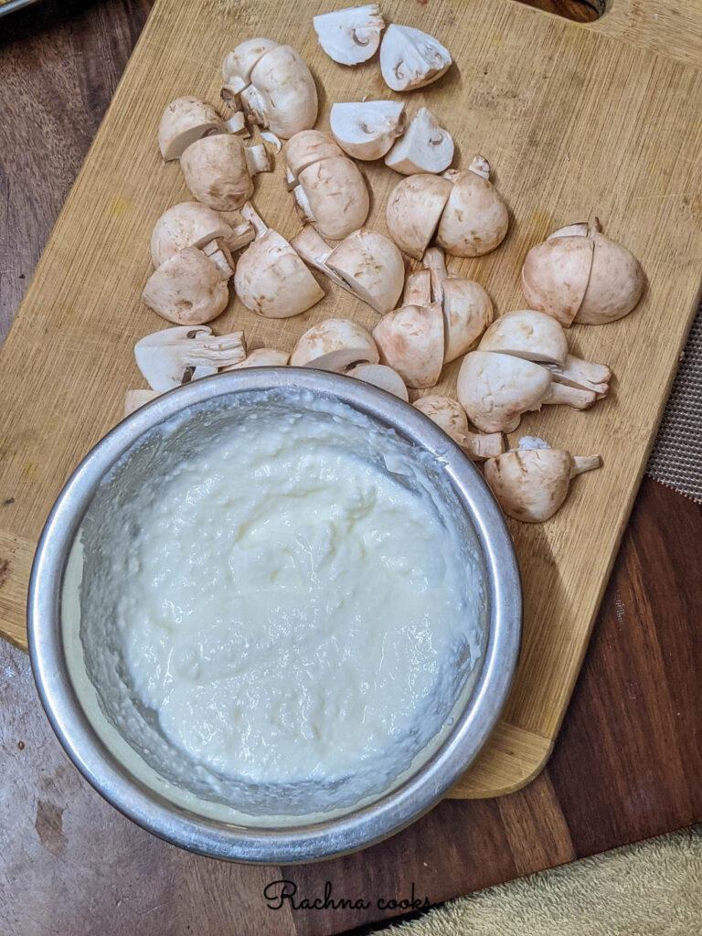 Button mushrooms cut into quarters with a bowl of greek yogurt.