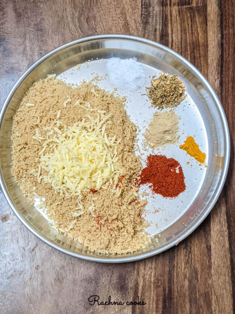 Breadcrumbs, grated cheese, cayenne, garlic powder, italian seasoning, salt and turmeric in a plate.