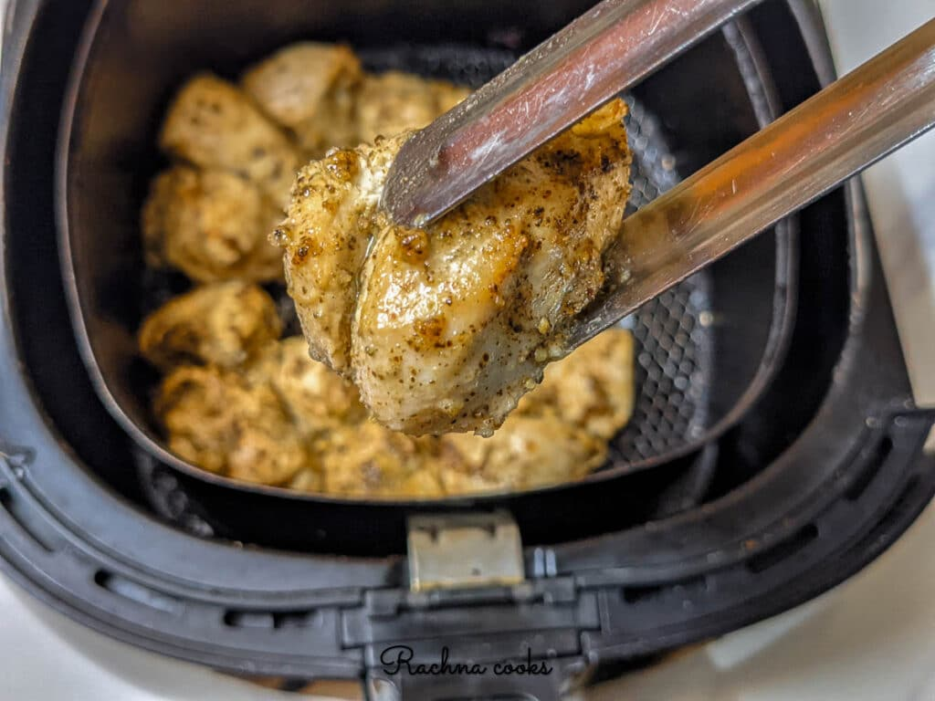 Delicious air fried lemon pepper chicken after air frying in air fryer basket.