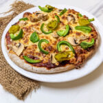 Delicious personal pizza done in air fryer on a white plate.