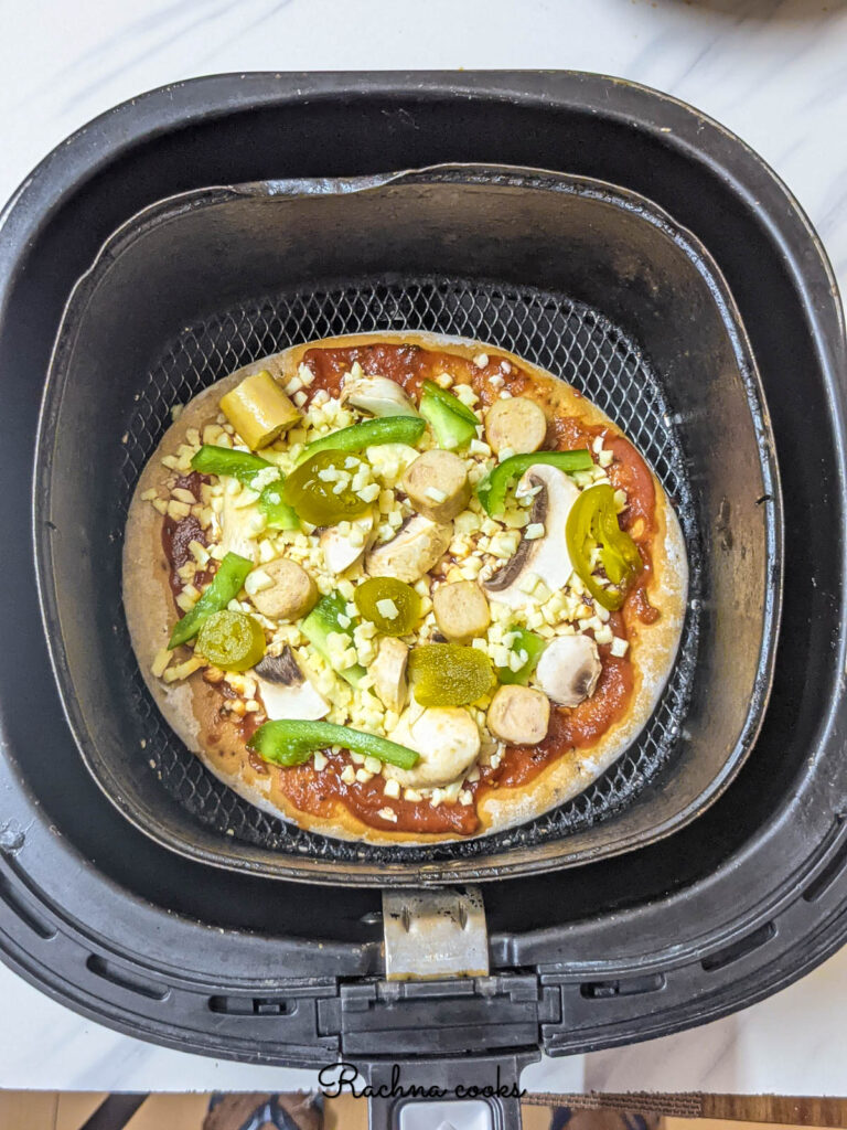 A pizza pie with tomato sauce, cheese and toppings ready for air frying kept in air fryer basket.