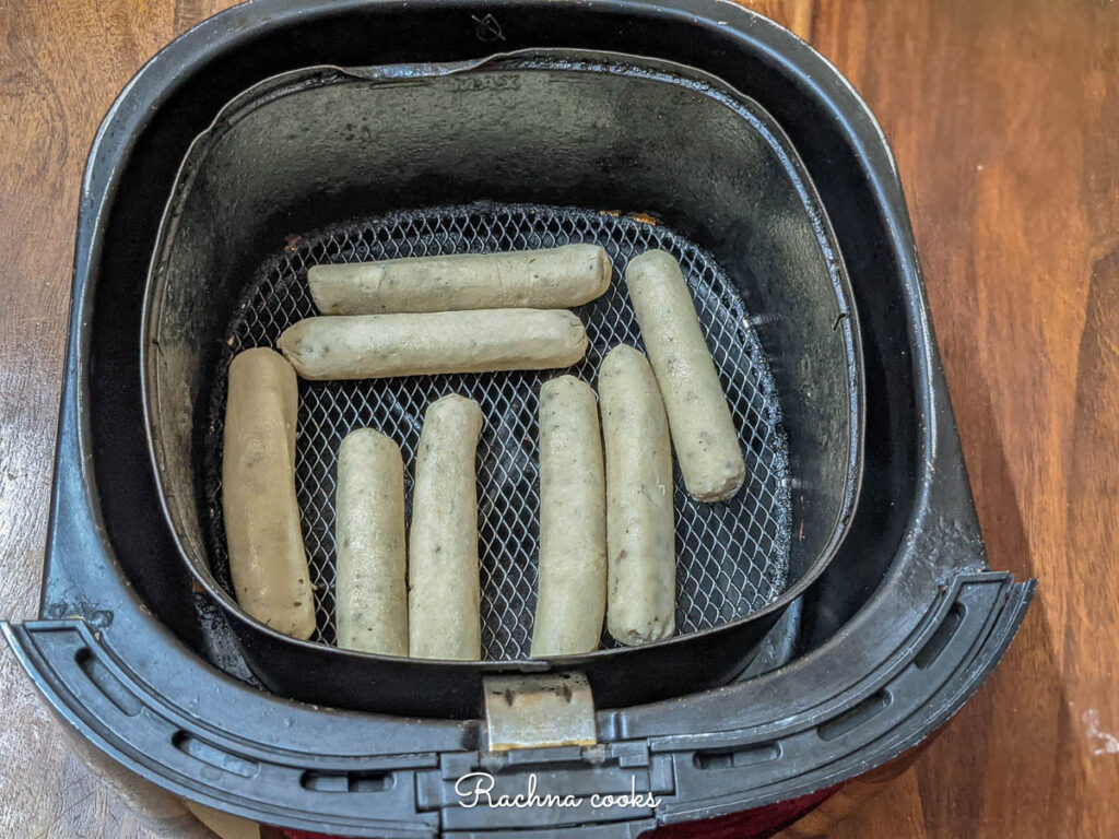 Thawed sausages in air fryer ready for air frying.
