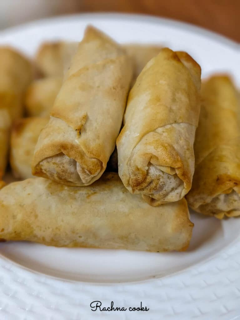 Close up of air fried spring rolls on a white plate.