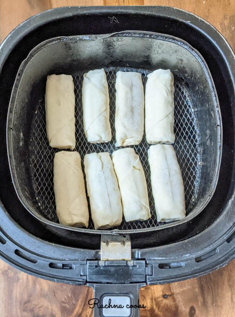 frozen spring rolls kept in air fryer for air frying.