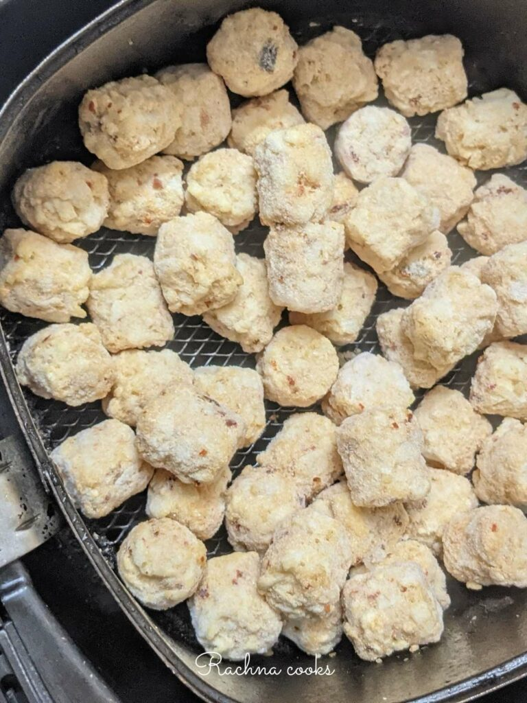 Frozen tater tots in air fryer basket ready for air frying.