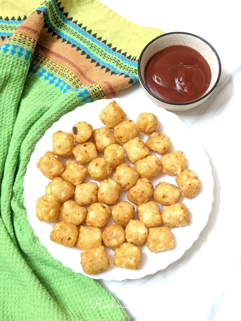 Tasty golden tater tots on a white plate.