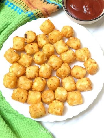 Crispy tater tots in a white plate with ketchup