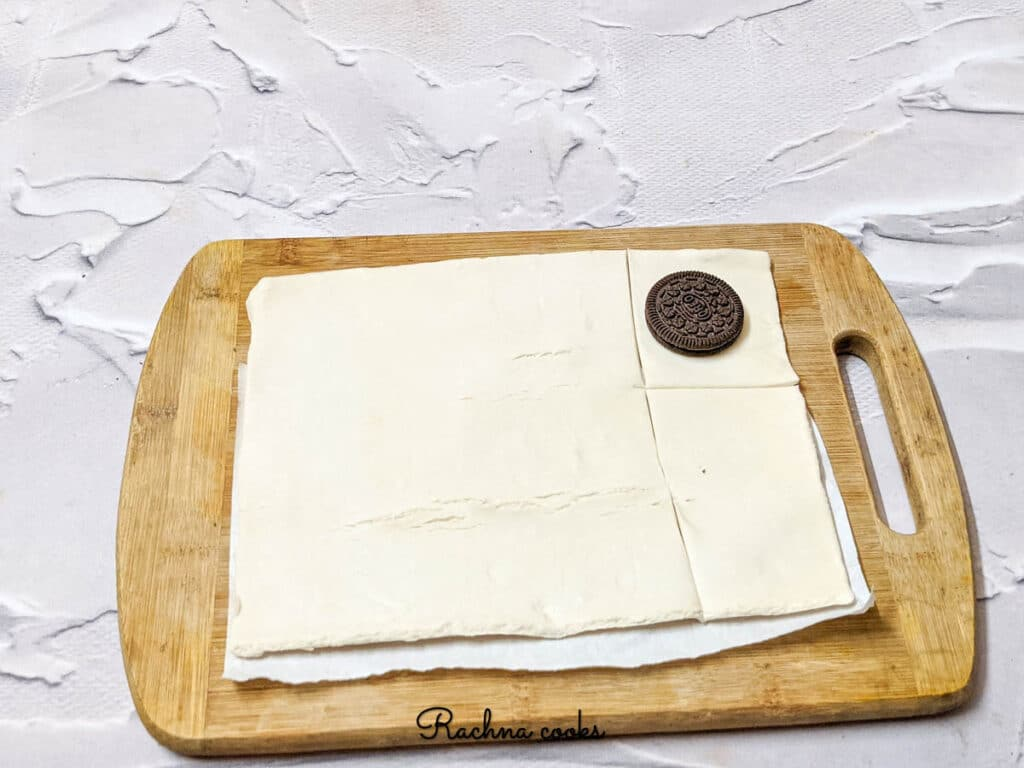 A pastry sheet placed on a chopping board with an Oreo placed in the corner and a square cut made around it.