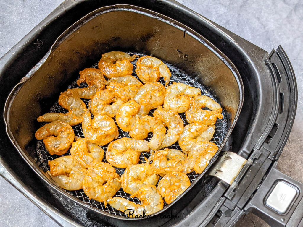 Marinated shrimp in one layer in preheat air fryer ready for air frying.