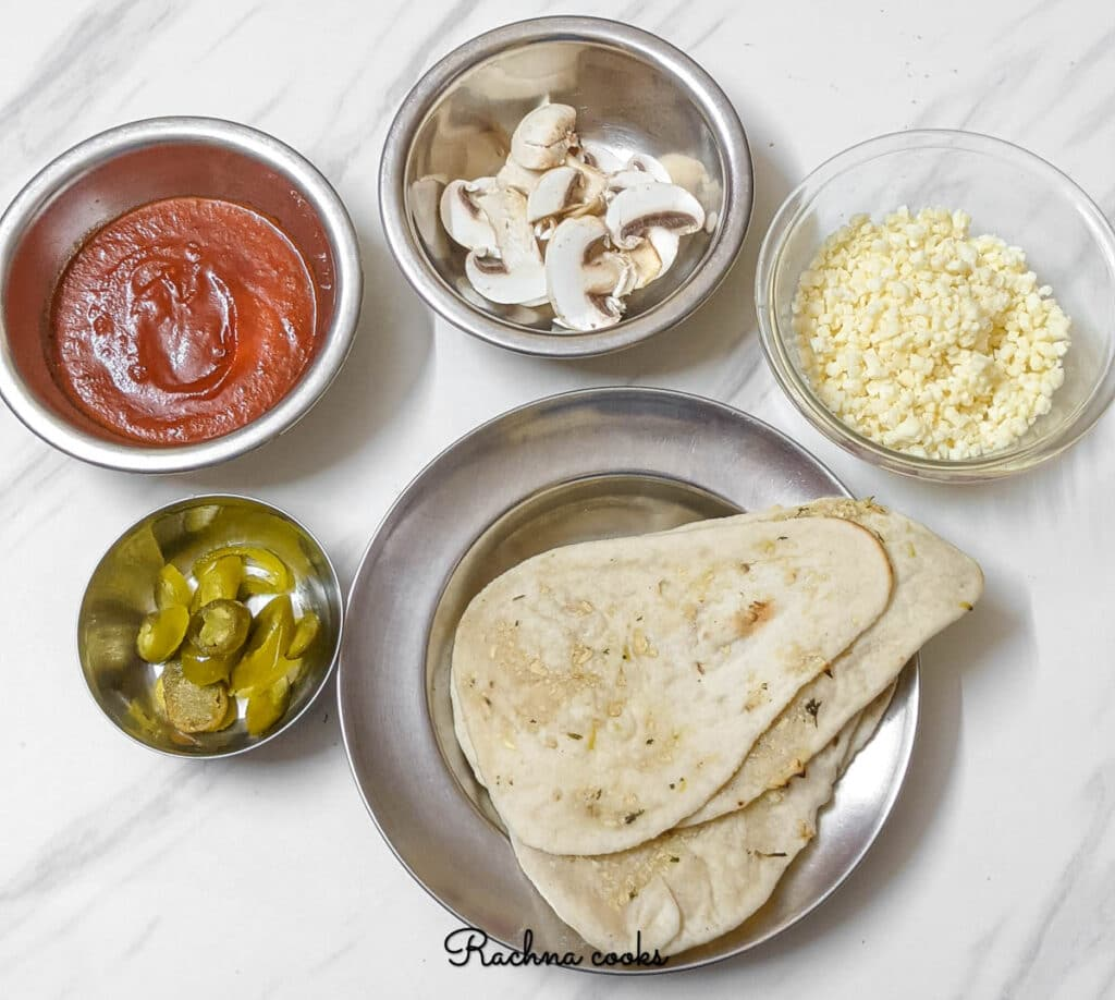 Ingredients for making naan pizza that include garlic naans, shredded mozzarella, tomato sauce and toppings.