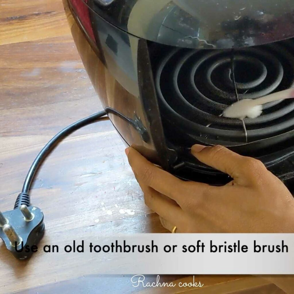 Use toothbrush to clean caked grease from air fryer heating coil.