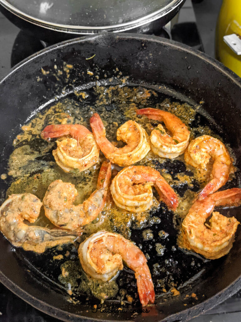 Tandoori shrimp being cooked in the skillet.