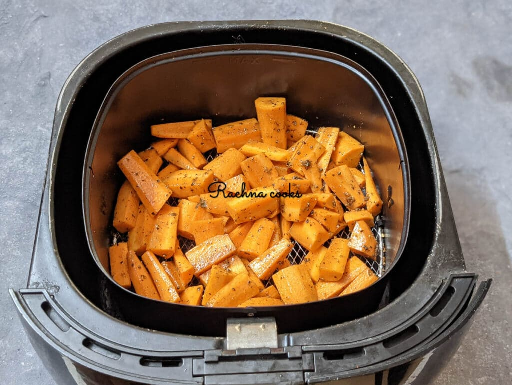 Preheated air fryer with marinated carrot chunks in basket.