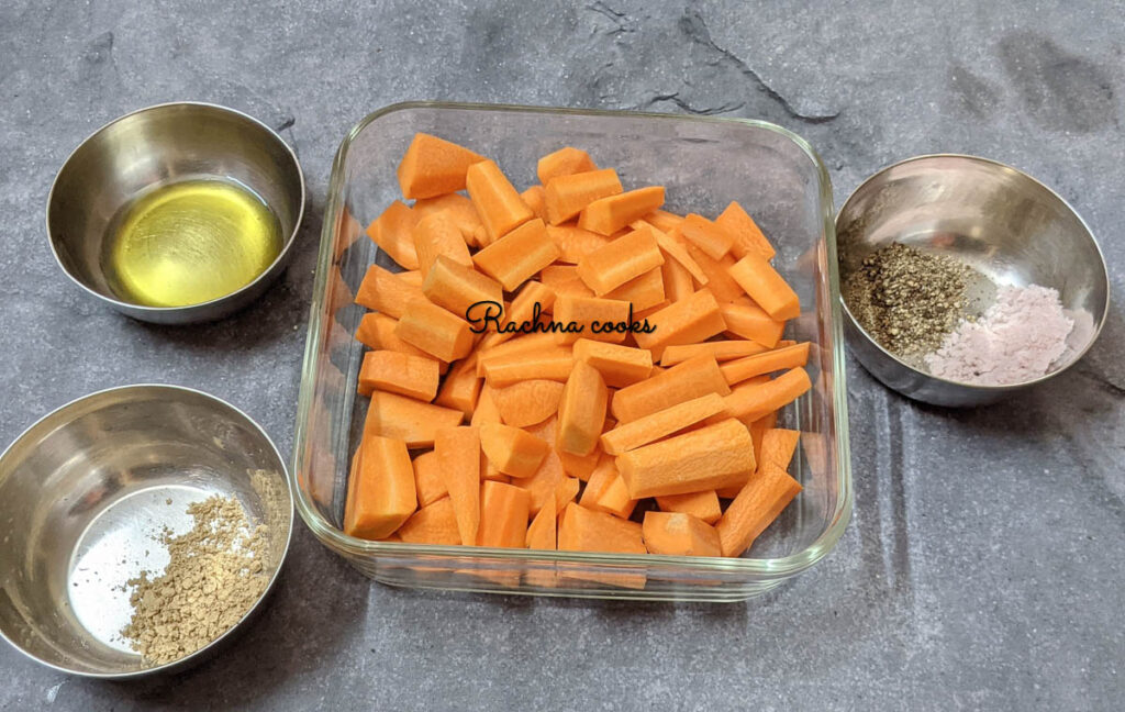 Bowls having garlic powder, pepper and Himalayan pink salt with olive oil and cut carrots.