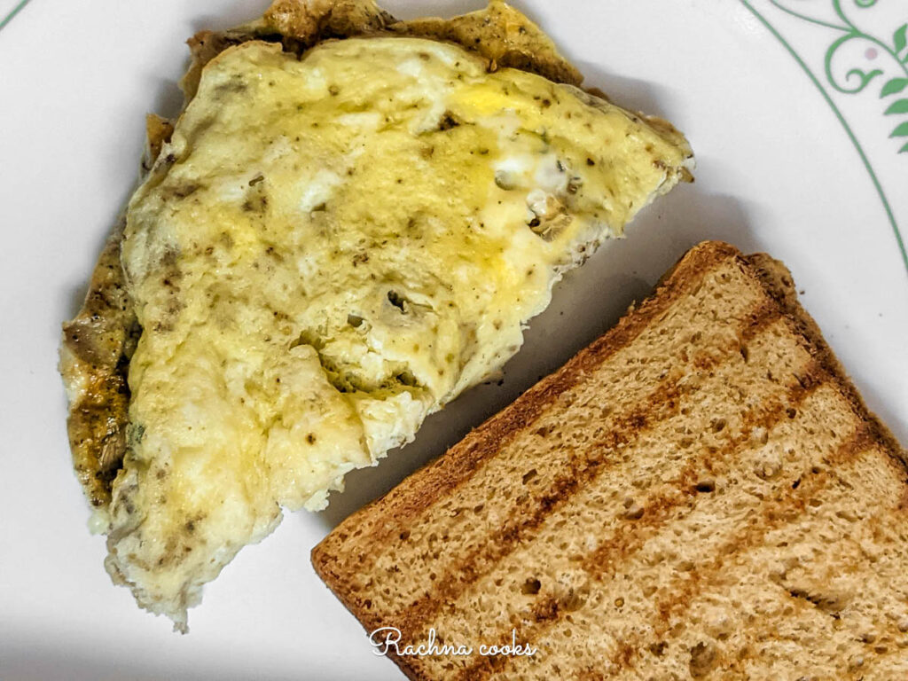 Top view of air fryer omelet on the plate with a slice of toasted bread.