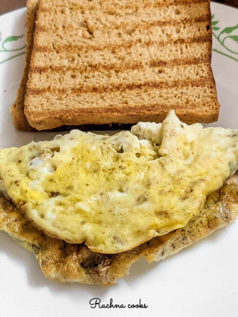 omelette on the plate with toasted bread slice.