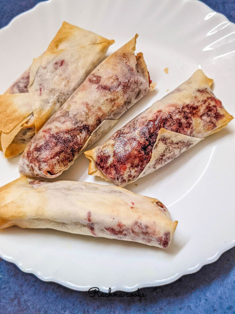 Delicious air fried spring rolls on a white plate.