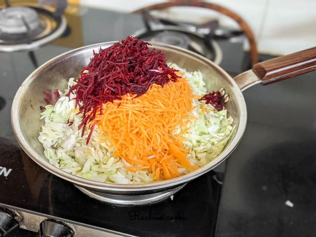 Grated cabbage, carrot and beetroot added to the pan for cooking.