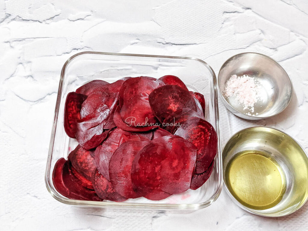 Sliced beetroot in a shallow plate with olive oil and pink Himalayan salt in bowls