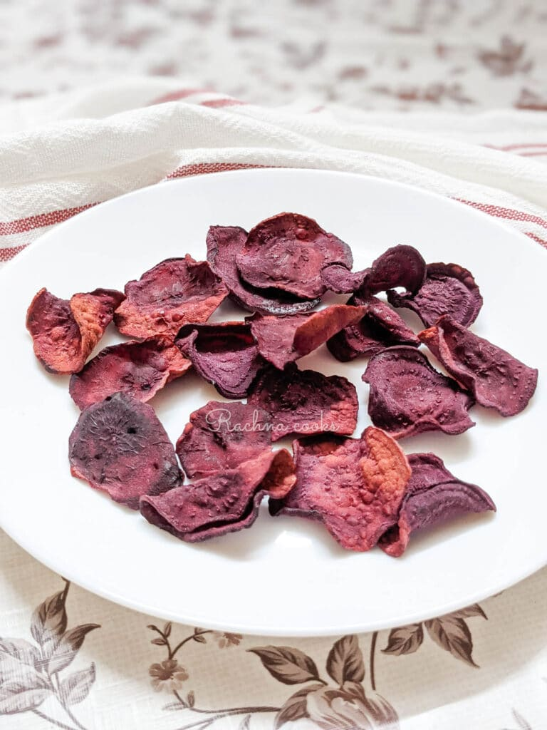 air fried beet chips on a white plate.