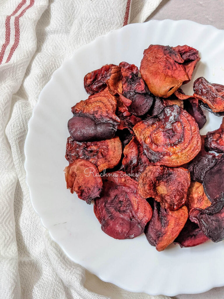 close up of air fried beet chips on a white plate.