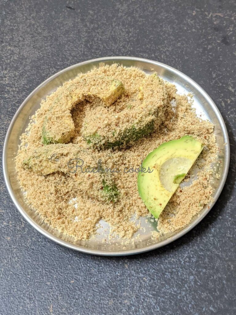avocado slice dipped in breading. One avocado slice without breading is also visible.