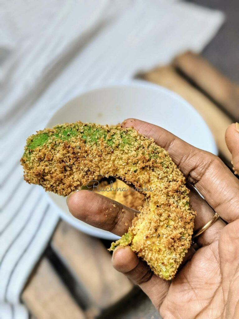 Close up of one avocado fry in hand after it has been air fried.