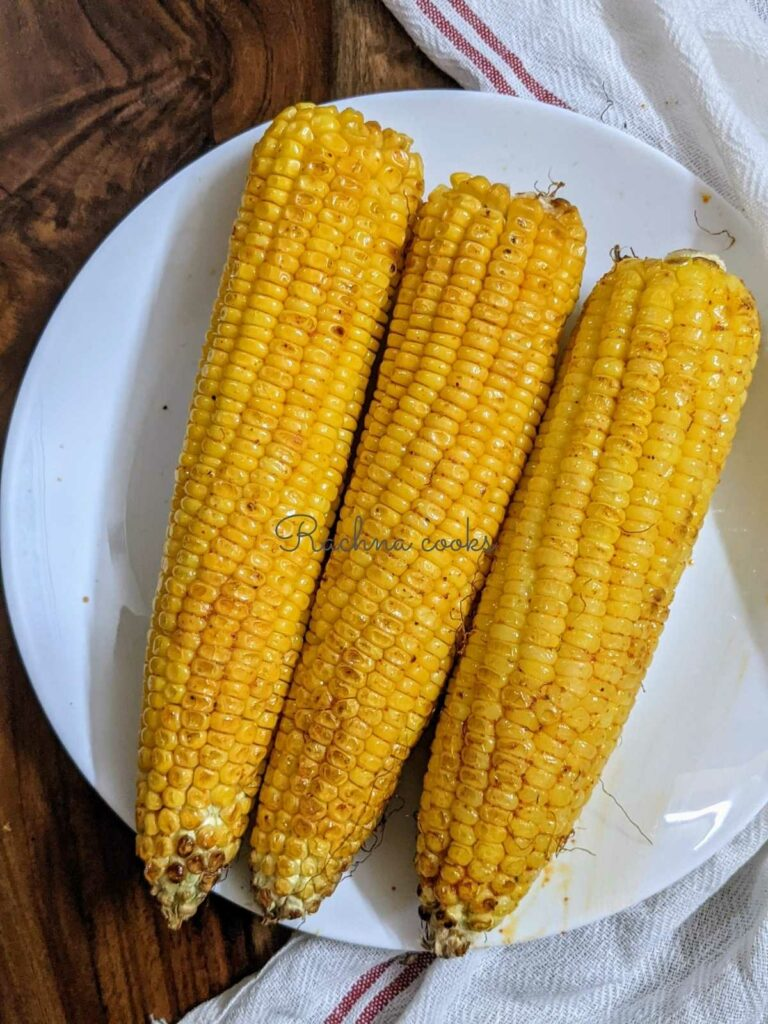 3 corn on the cob air fried and kept on a white plate.