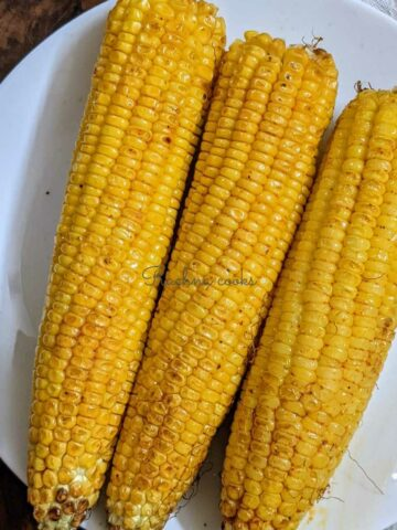 3 air fried corn on the cob on a white plate.