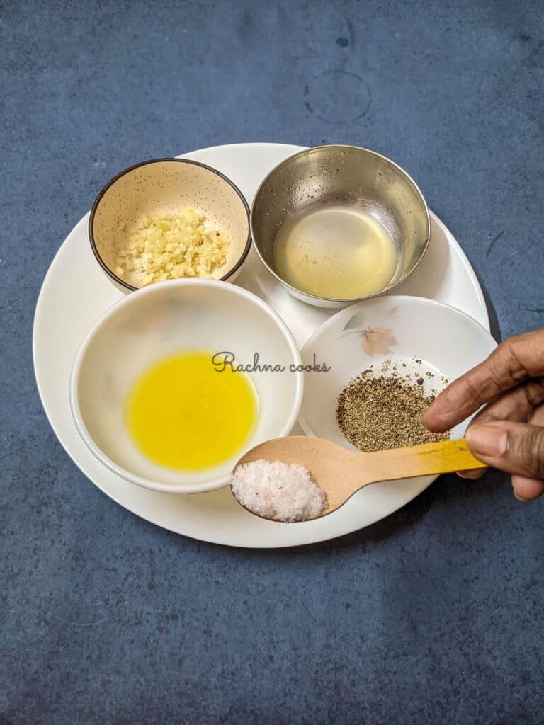 Bowls of olive oil, salt, pepper, lemon juice and minced garlic.
