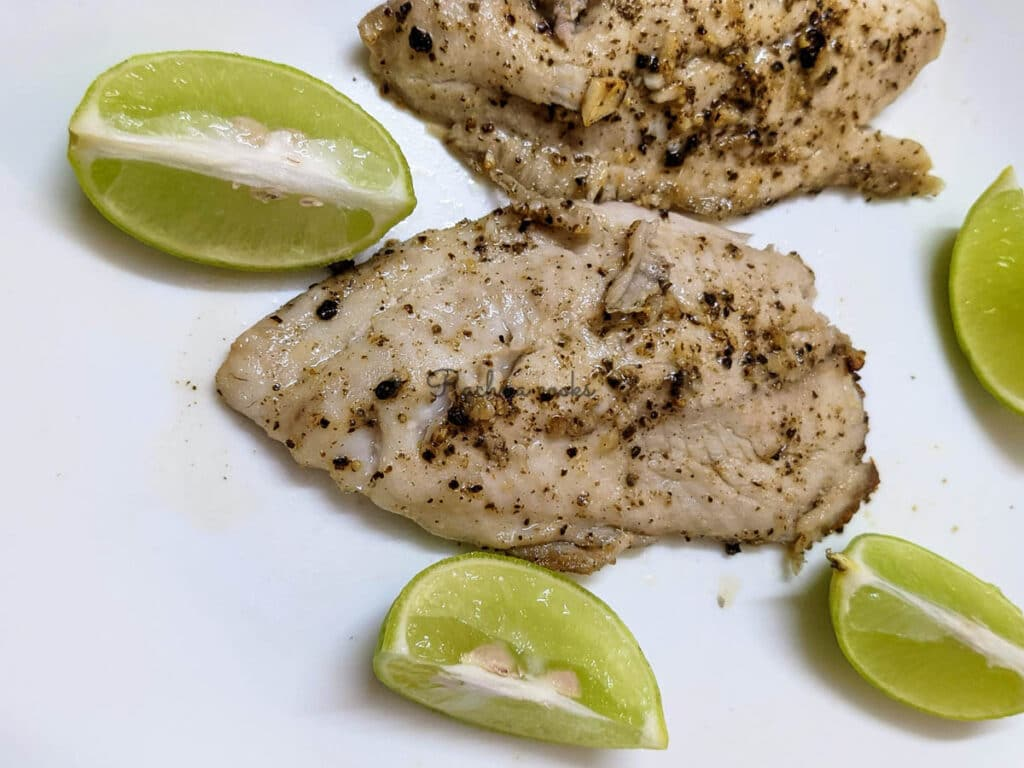 Tilapia fillets after air frying with lemon wedges on a white plate