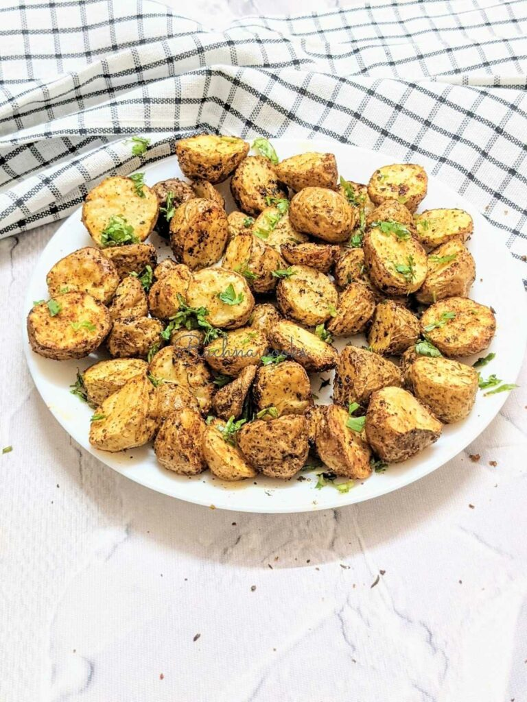 Delicious roasted baby potatoes done in air fryer on a white plate with a white background.