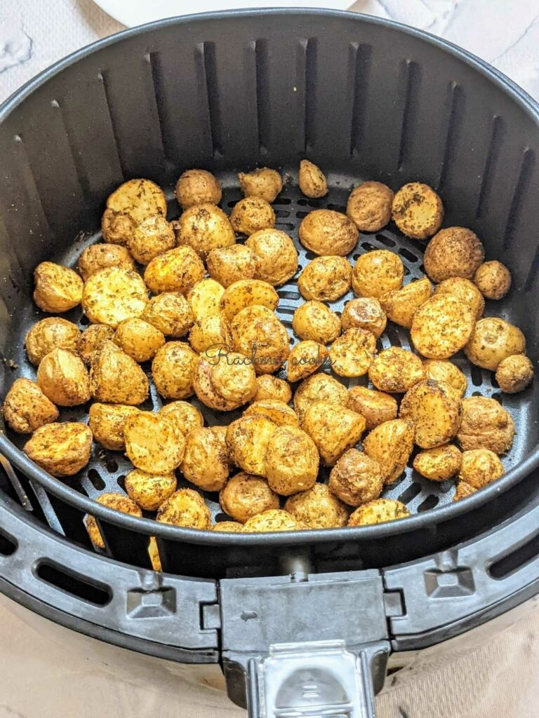 Roasted baby potatoes after air frying in air fryer basket.